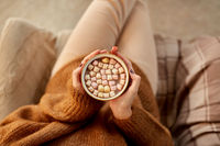 woman holding mug of hot chocolate and marshmallow