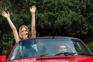 Happy woman having fun in cabriolet while her boyfriend driving