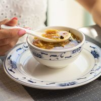 Woman eats chinese vegetable soup at restaurant