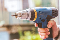 Do it yourself: Home Handyman is holding a cordless screwdriver, outdoors