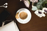 Cup of coffee, bouquet of anemone, purple roses, woman handbag, phone on table