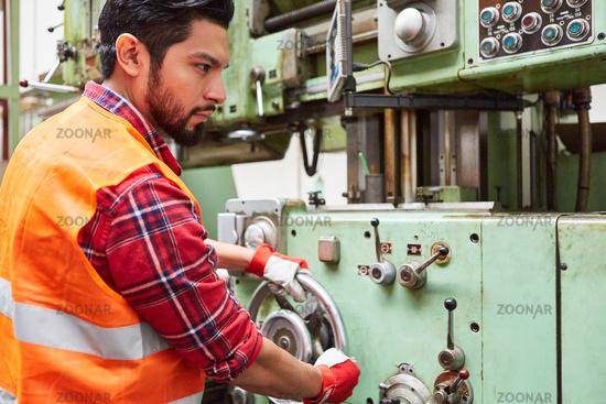 Arbeiter in Fabrik bedient eine Standbohrmaschine