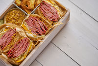 Enormous sandwiches with pastrami beef in wooden box. Served with baked potatoes, pickles