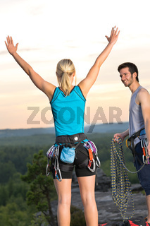 Rock climbing cheerful alpiners on top sunset