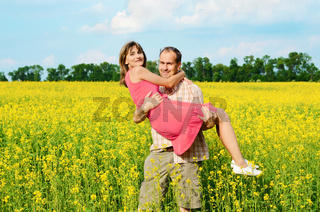 Happy man and woman in yellow meadow