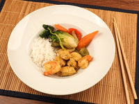 Red Thai curry with chicken and shrimps with fried vegetables and rice
