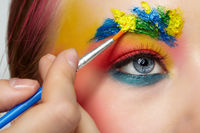 Artist's hand with paintbrush painting beautiful teen girl's brows make-up.