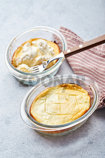 Delicious cottage cheese casserole in portioned glass forms with sour cream. Traditional Russian cuisine for breakfast - Zapekanka