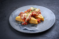 Modern style traditional Italian polenta alla sarda con salsiccia with meat sausage served as close-up on a Nordic design plate with copy space