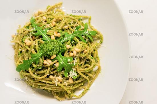 Mediterranean spaghetti with basil arugula pesto decorated with roasted pine nuts and fresh rocket salad