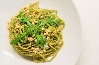 Mediterranean spaghetti with basil arugula pesto decorated with roasted pine nuts and fresh rocket salad
