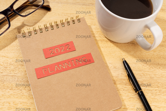 New year 2022 planning concept. Notepad, cup of coffee and eyeglasses on wooden desk