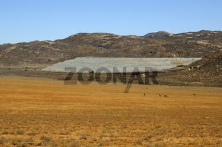 Damm aus grauem Abraum eines stillgelegten Kupferbergwerks