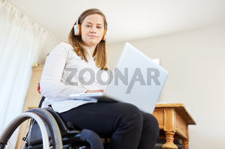 Frau mit Behinderung im Rollstuhl mit Laptop Computer
