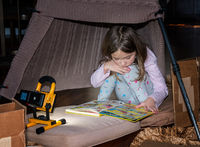 Small school age girl playing in homemade tent and reading a comic book