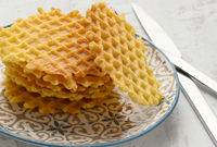 stack of baked Belgian waffles on a round plate on a white table, delicious breakfast
