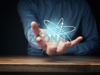 Everything is energy, businessman holding energetic ball, positive energy symbolized by atoms flying around