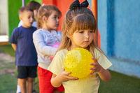 Kleines Mädchen mit Ball beim Kinderturnen