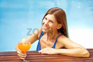 Ältere Frau mit Cocktail im Pool