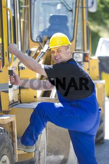 Bauarbeiter steigt in eine Baumaschine ein