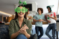 Portrait of caucasian woman wearing deely boppers and glasses celebrating st patrick's at a bar