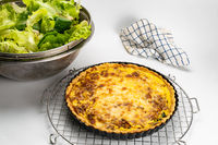 Freshly baked quiche  in black metal oven pie baking plate on a metal cooling rack.