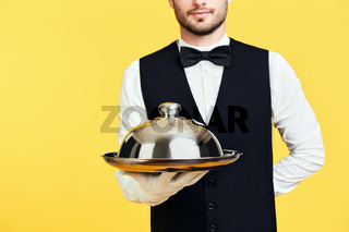 Young handsome waiter holding metal tray with cover ready to serve