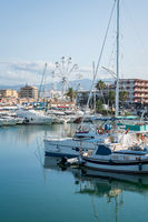 Boats in the port with view on the city coastline with ferris wheel in Gandia, Spain