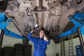 Repairman under car gesturing thumbs up