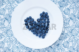 blueberries in a heart shape on a white plate
