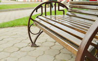Close-up of a part of a new wooden brown bench with metal handrails, outdoors