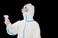 Female doctors in medical protective clothing take temperature