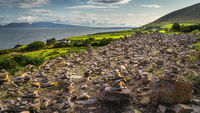 Field with many rock piles, rock balancing with a view on Dingle peninsula