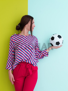 Portrait of young European woman holding soccer ball on her palm