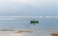 Fisherman in traditional wooden canoe and moterboat in lake Atitlan during sunset in San Pedro la Laguna, Guatemala