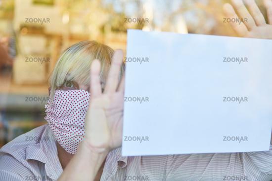 Seniorin in Quarantäne hält Hilferuf ans Fenster bei Coronavirus Pandemie