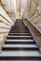 Wooden old weathered staircase going up with wooden handrail, between two stone bricks walls, in abandoned building