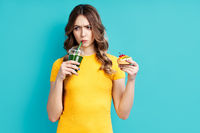 Unhappy woman on dieting drinking detox juice holding cake in hand choosing healthy food
