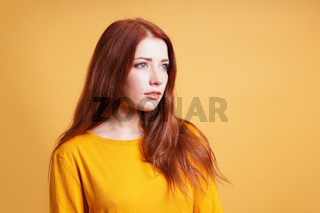 young woman with blank expression contemplating thought