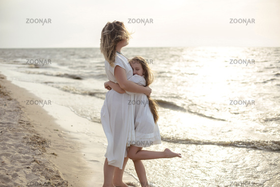 Mother and daughter hugging near sea
