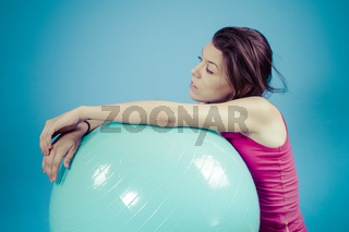 Young girl with big blue fit ball, on white chroma background
