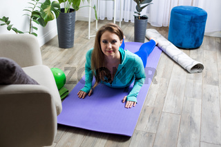 the woman practices yoga at home while quarantine