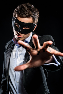 Elegant man wearing black mask posing indoors