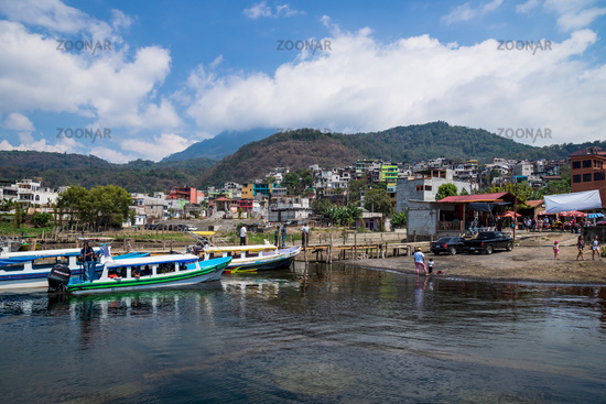 Jetty at the coast of lake Atitlan with view on colorful houses in Santiago Atitlan, Guatemala