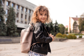 The little girl is walking around the city with a bag