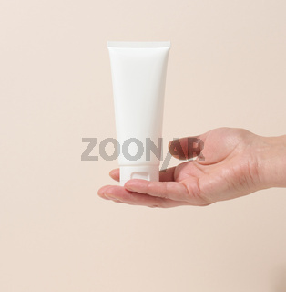 female hand holds empty white plastic tubes for cosmetics. Packaging for cream, gel, serum, advertising and product promotion, mock up