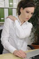 Frau im Büo hat Nackenschmerzen