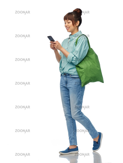 woman with phone and reusable food shopping bag