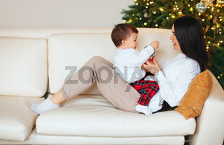 Mother playing with son near Christmas tree