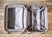 Open suitcase isolated on old wooden background